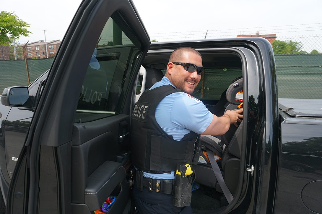 UIC Police Officer pointing to a properly installed child safety seat.