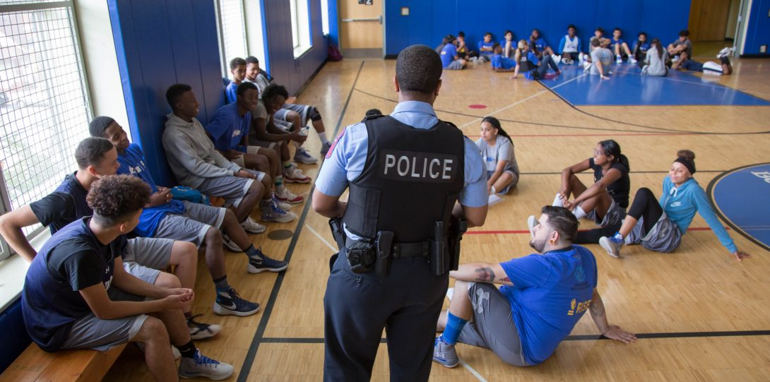 Officer speaking to young people on basketball court