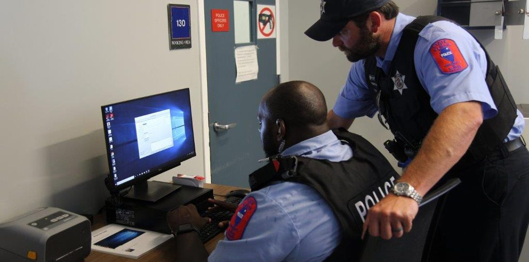 Two officers looking at a computer screen