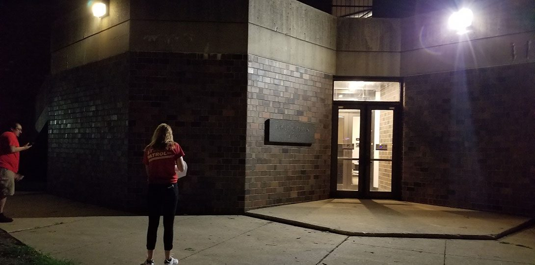 Student Patrol member conducting light survey outside of building on campus