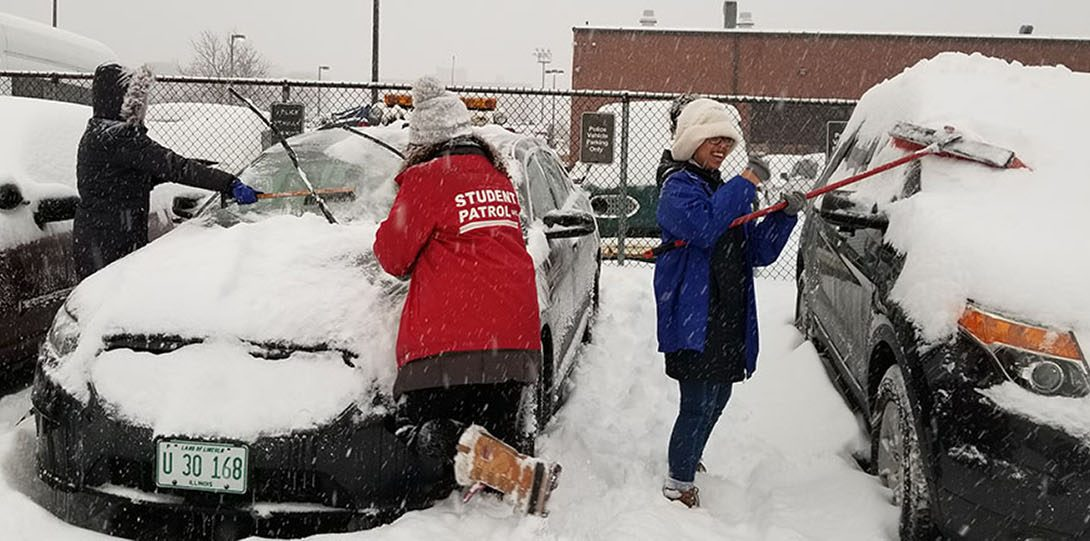 Student Patrol Members cleaning snow off cars