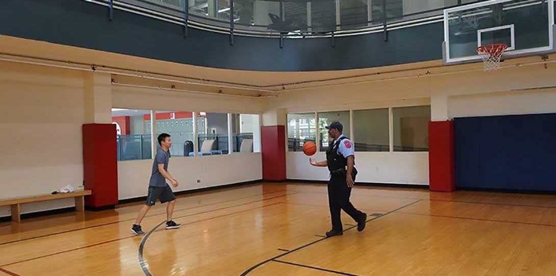 UIC PD officer playing basketball with student